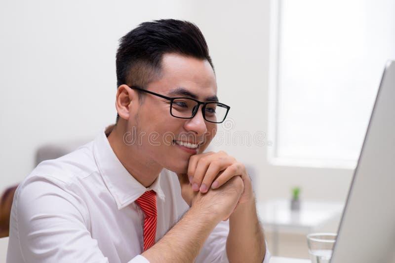 Hombre de negocios joven que trabaja en oficina, sent?ndose en el escritorio, mirando la pantalla del ordenador port?til, sonrien imágenes de archivo libres de regalías