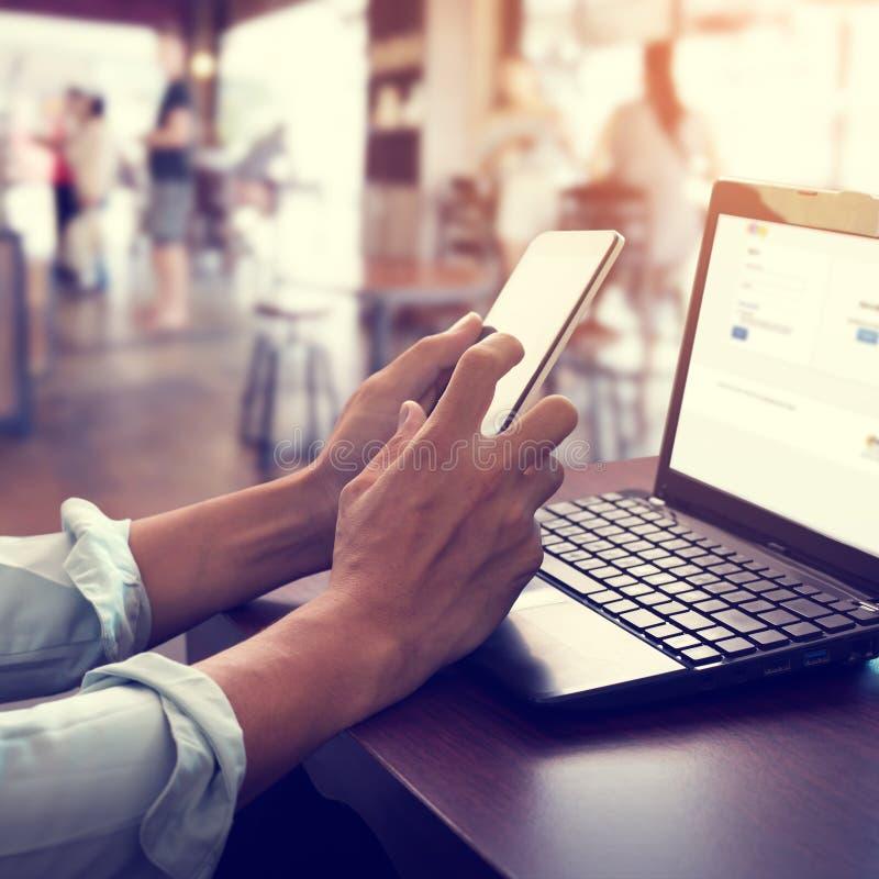 hombre de negocios joven que trabaja en su ordenador portátil y que usa el teléfono elegante que se sienta en la tabla de madera  imágenes de archivo libres de regalías