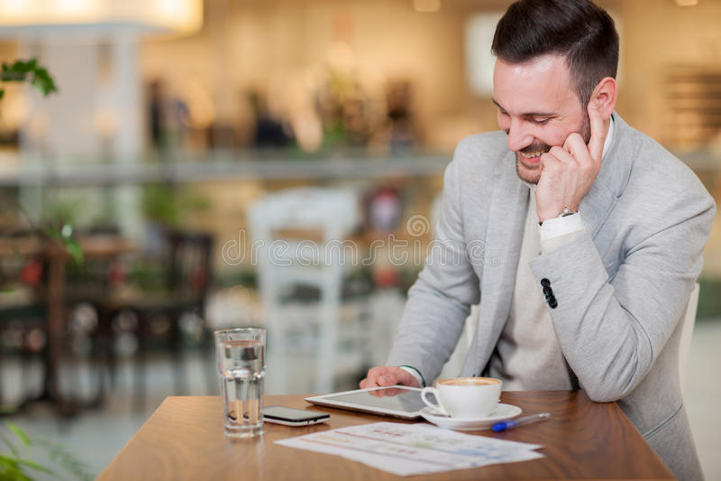 Hombre de negocios joven que trabaja en una tableta digital en un café imagen de archivo