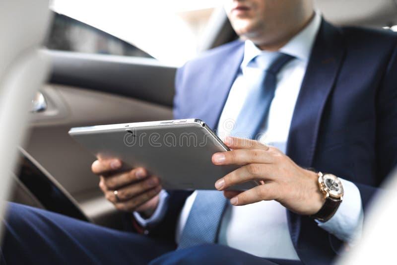 Hombre de negocios joven que usa la PC de la tableta mientras que se sienta en asiento trasero de un coche E foto de archivo libre de regalías