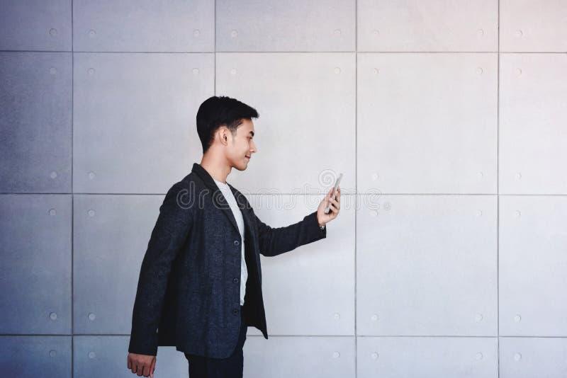 Hombre de negocios joven Reading Message de la motivación vía paseo elegante del rato del teléfono foto de archivo libre de regalías