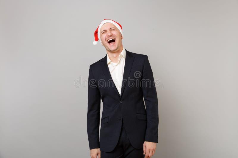 Hombre de negocios joven de risa en el traje negro clásico, sombrero de la Navidad aislado en fondo gris de la pared en estudio l imágenes de archivo libres de regalías