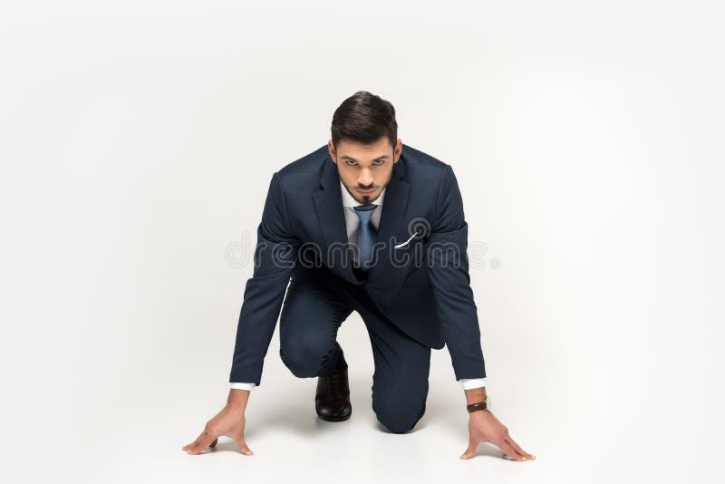 hombre de negocios joven serio en la posición de salida lista para correr imagen de archivo