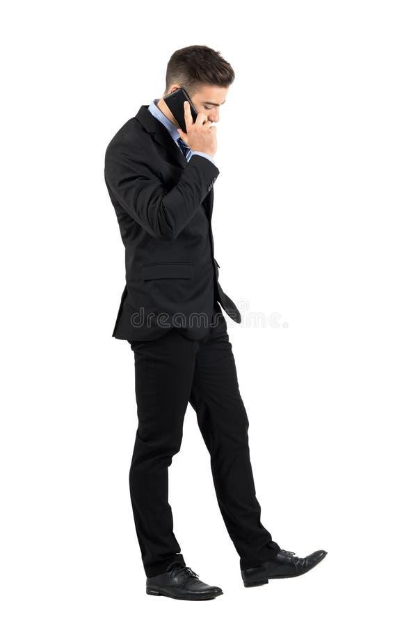 Hombre de negocios joven serio que camina y que habla en su vista lateral del teléfono móvil fotografía de archivo