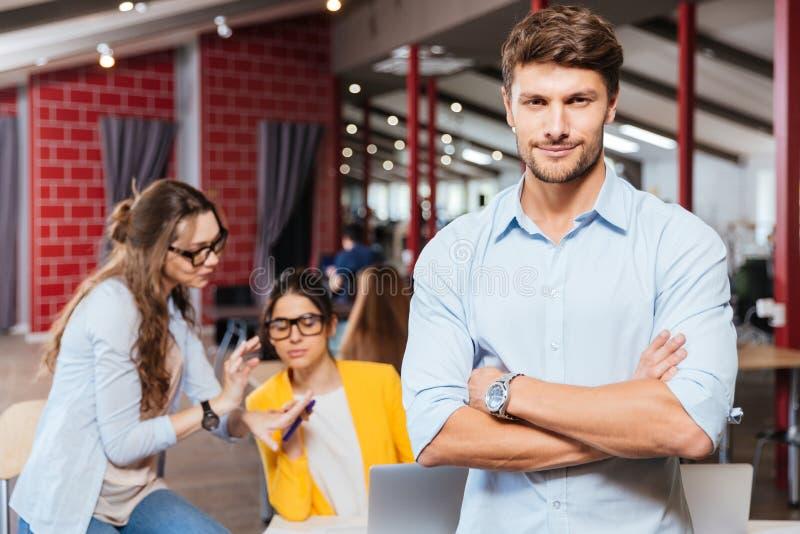 Hombre de negocios joven serio que se coloca con los brazos cruzados foto de archivo libre de regalías