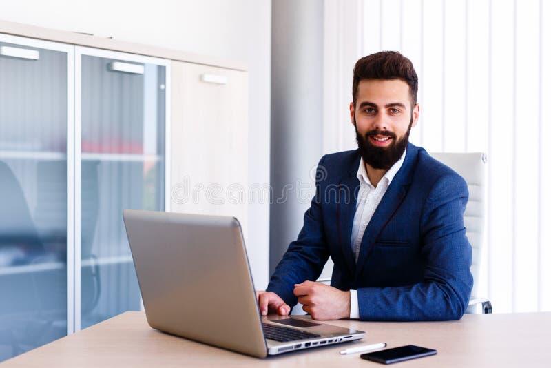 Hombre de negocios joven Smiles While Working en la oficina fotografía de archivo libre de regalías