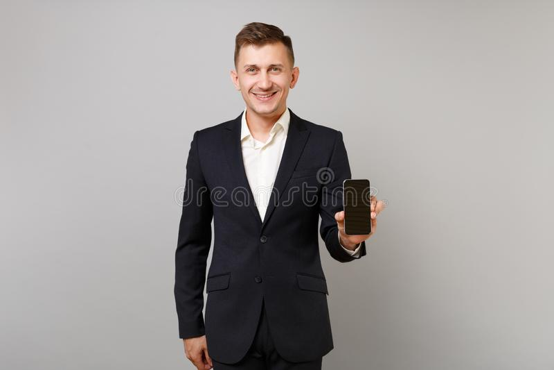 Hombre de negocios joven sonriente en el traje negro clásico, camisa que sostiene el teléfono móvil con la pantalla vacía en blan fotos de archivo libres de regalías