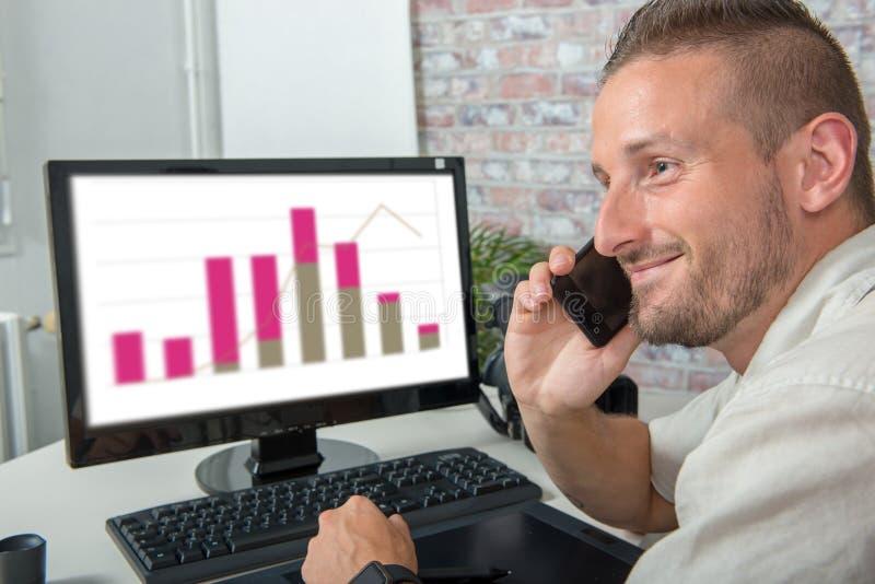 Hombre de negocios joven sonriente en la oficina que habla en el teléfono fotos de archivo libres de regalías
