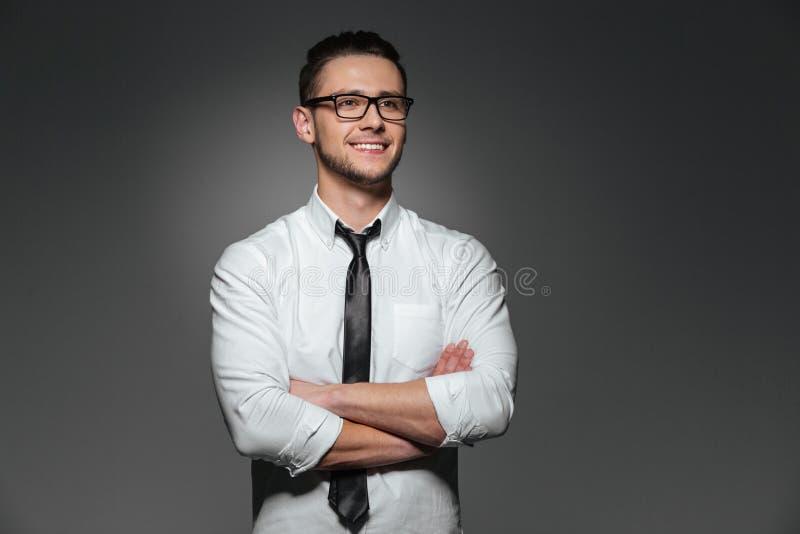 Hombre de negocios joven sonriente en los vidrios que se colocan con los brazos cruzados imagen de archivo libre de regalías