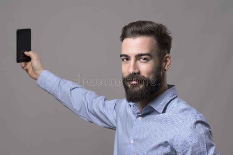 Hombre de negocios joven sonriente feliz que sostiene el teléfono móvil que toma el selfie que mira la cámara fotografía de archivo