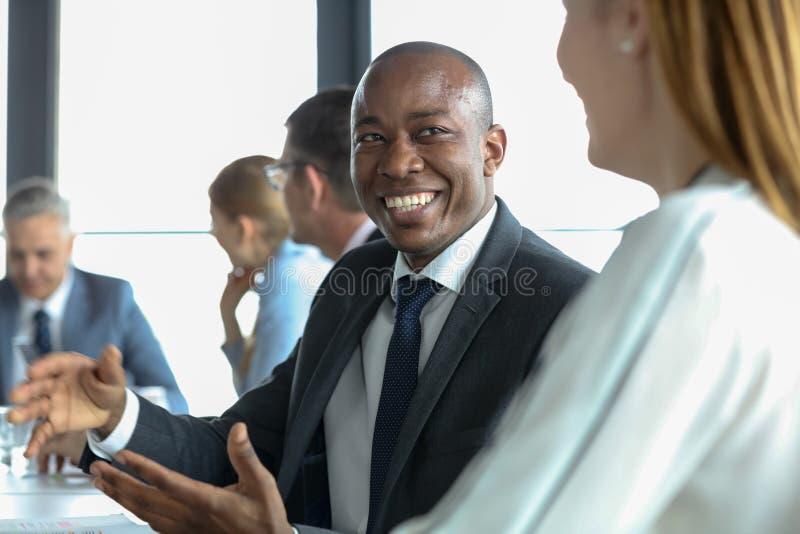 Hombre de negocios joven sonriente que discute con el colega femenino en sala de juntas fotos de archivo