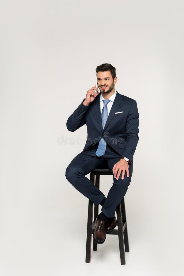 hombre de negocios joven sonriente que habla en smartphone mientras que se sienta en taburete y mira lejos foto de archivo libre de regalías