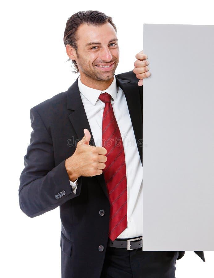 Hombre de negocios joven sonriente que lleva a cabo un cartel imagen de archivo