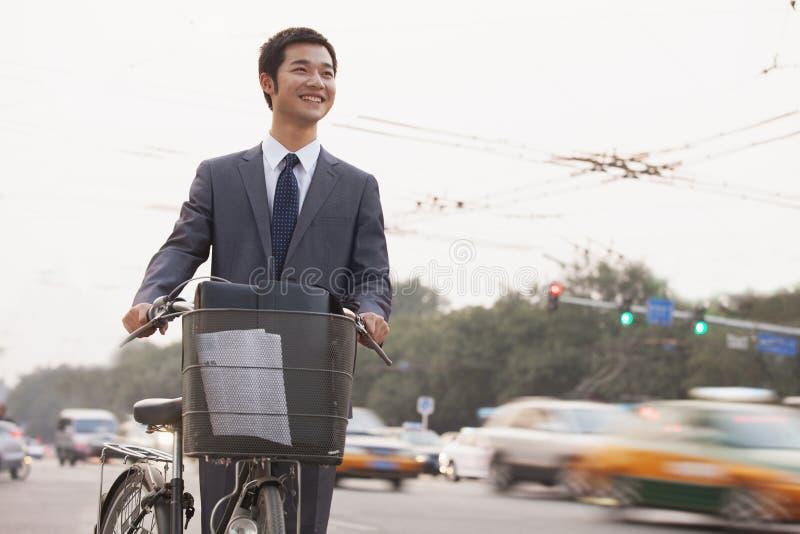 Hombre de negocios joven, sonriente que monta una bicicleta en la calle con los coches que apresuran cerca en Pekín, China imagen de archivo libre de regalías