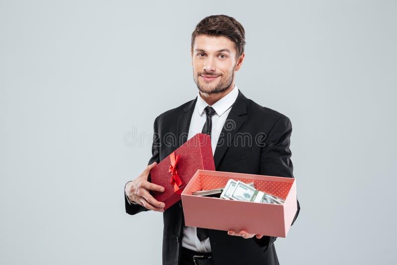 Hombre de negocios joven sonriente que muestra la actual caja por completo de dinero imagen de archivo libre de regalías