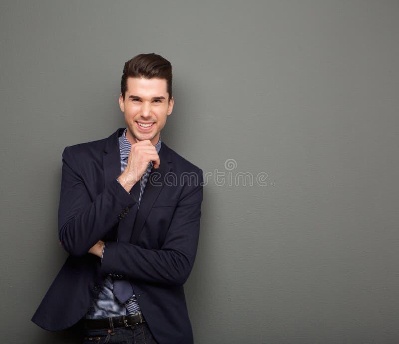 Hombre de negocios joven sonriente que se coloca con la mano a la barbilla fotografía de archivo libre de regalías