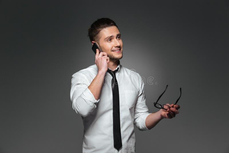 Hombre de negocios joven sonriente que sostiene los vidrios y que habla en el teléfono celular imagen de archivo libre de regalías