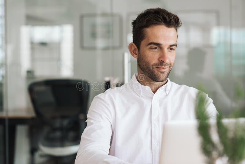 Hombre de negocios joven sonriente que trabaja en un ordenador portátil en su escritorio fotografía de archivo libre de regalías