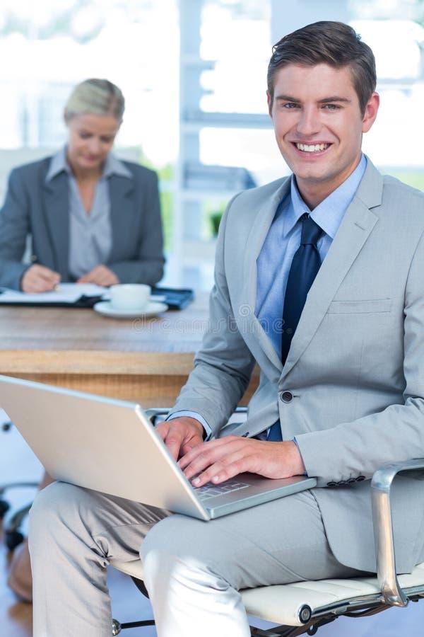 Hombre de negocios joven sonriente usando su ordenador portátil fotos de archivo