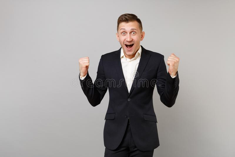 Hombre de negocios joven sorprendido en el traje negro clásico, camisa que hace el gesto del ganador que mantiene abierto de par  foto de archivo
