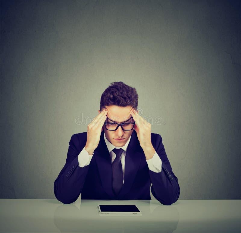 Hombre de negocios joven subrayado que se sienta en el escritorio con la tableta fotos de archivo libres de regalías