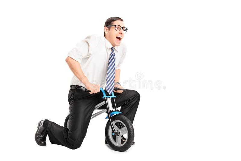 Hombre de negocios joven tonto que monta una pequeña bici imágenes de archivo libres de regalías