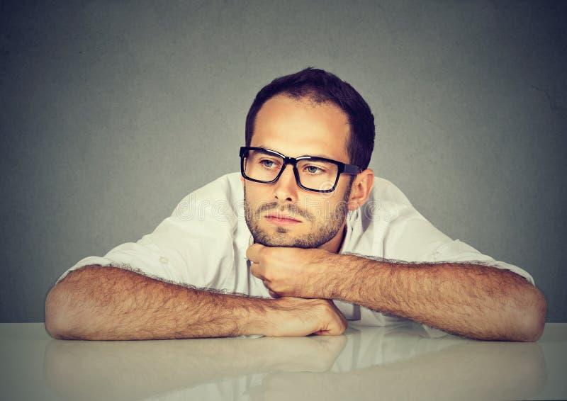 Hombre de negocios joven triste desesperado que se inclina en un escritorio foto de archivo libre de regalías