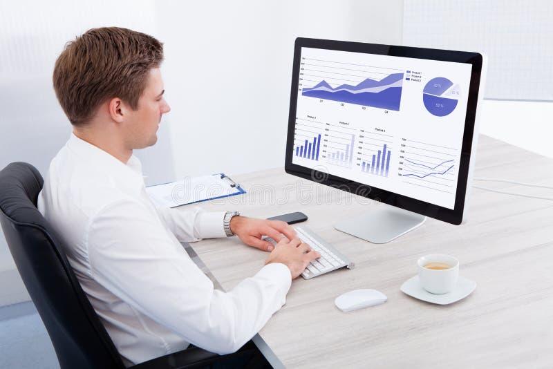 Hombre de negocios joven usando el ordenador en el escritorio imagen de archivo libre de regalías