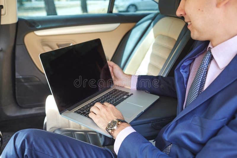 Hombre de negocios joven usando el ordenador portátil en el asiento trasero del coche fotografía de archivo