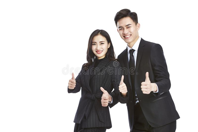 Hombre de negocios joven y empresaria asiáticos que muestran los dos-pulgares imágenes de archivo libres de regalías