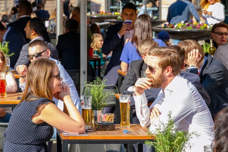 Hombre de negocios joven y empresarias que beben en un al aire libre lleno foto de archivo
