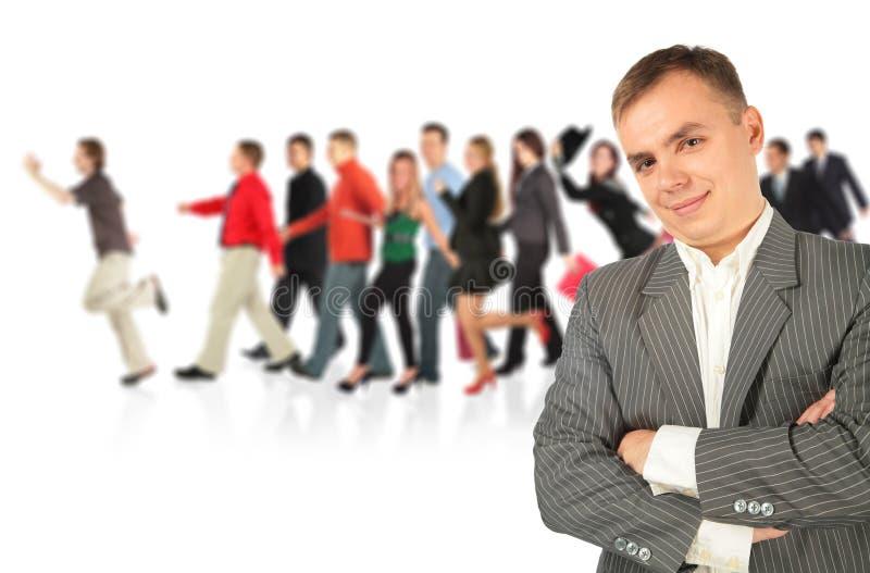 Hombre de negocios joven y grupo que recorre imagen de archivo libre de regalías