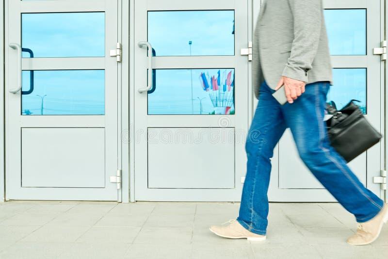 Hombre de negocios de la cosecha que camina cerca de la entrada del edificio fotos de archivo