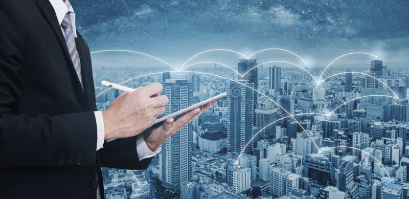 Hombre de negocios de la exposición doble que usa la tableta digital, y paisaje urbano Red del negocio, tecnología del blockchain foto de archivo