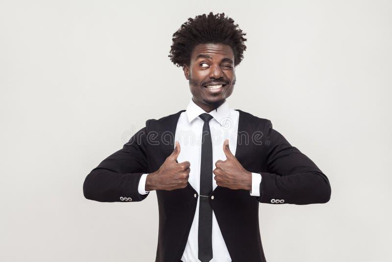 Hombre de negocios de la felicidad que mira la cámara y los pulgares para arriba imagen de archivo libre de regalías