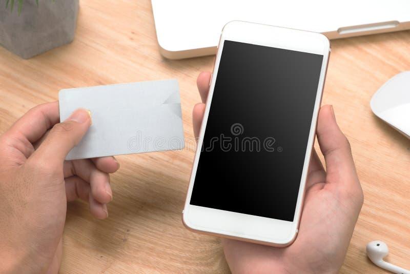 Hombre de negocios de la foto del primer que sostiene la tarjeta de crédito de la mano y que usa sma foto de archivo