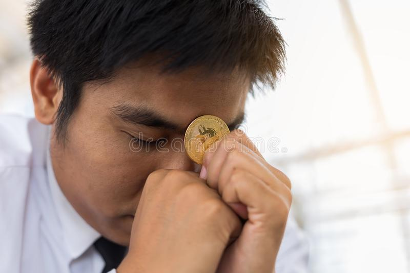 Hombre de negocios de la tensión que lleva a cabo el bitcoin foto de archivo