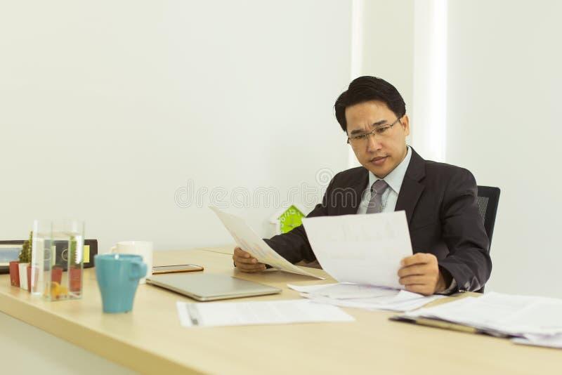 Hombre de negocios de la tensión que trabaja en su escritorio de oficina fotos de archivo