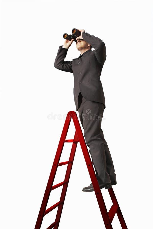 Hombre de negocios On Ladder Looking a través de los prismáticos imagenes de archivo