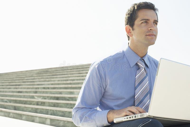 Hombre de negocios With Laptop Sitting en escalera contra el cielo imagen de archivo libre de regalías