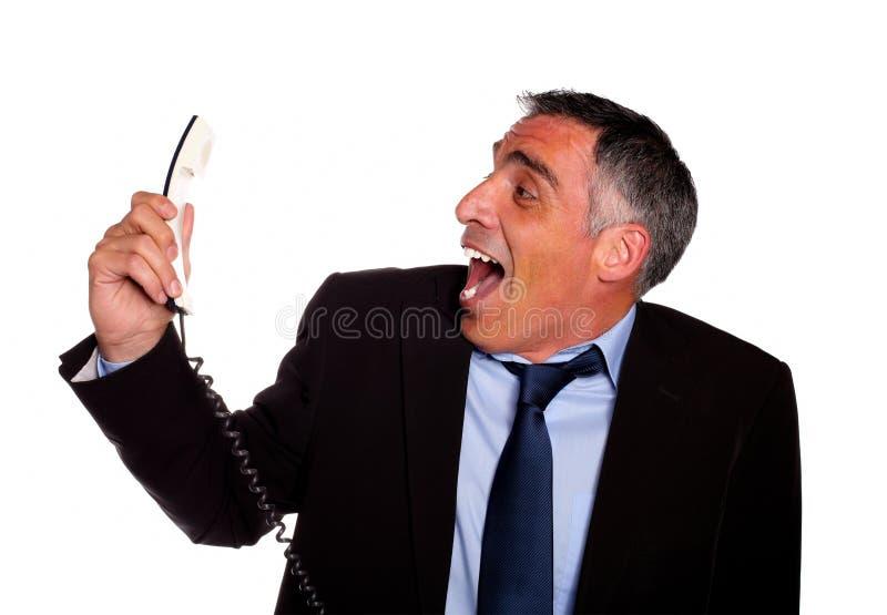 Hombre de negocios latino que ríe con un teléfono fotos de archivo libres de regalías