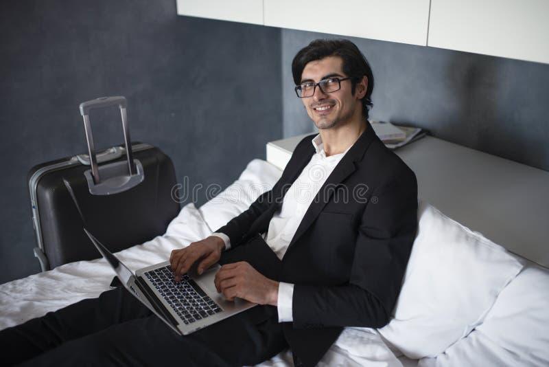 Hombre de negocios listo para viajar trabajos con su ordenador port?til foto de archivo