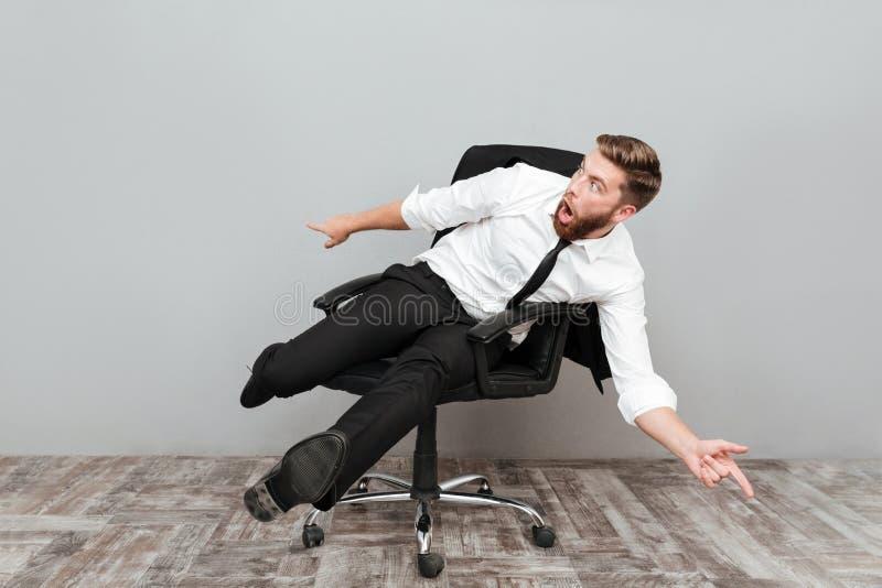 Hombre de negocios loco divertido que se divierte mientras que se sienta en silla de la oficina imagen de archivo