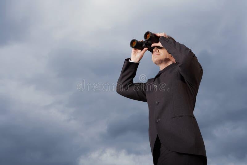 Hombre de negocios Looking Through Binoculars contra el cielo imagenes de archivo