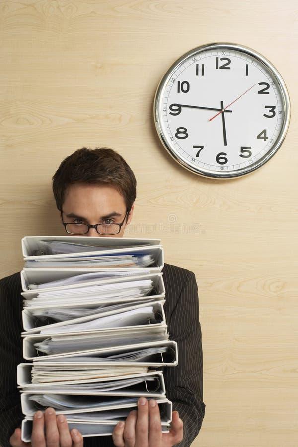 Hombre de negocios Looking At Clock en la pared de madera imagen de archivo
