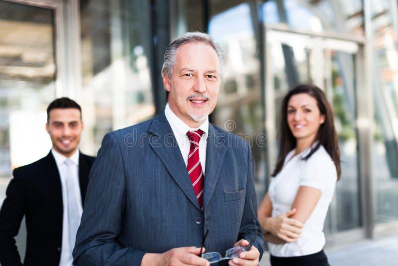 Hombre de negocios maduro delante de un grupo de hombres de negocios al aire libre fotos de archivo