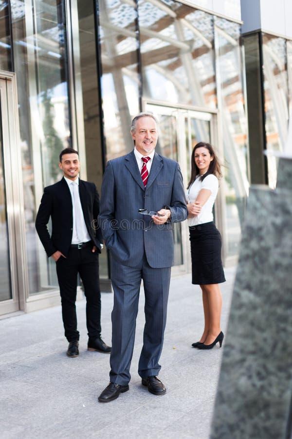 Hombre de negocios maduro delante de un grupo de hombres de negocios al aire libre foto de archivo libre de regalías