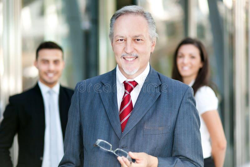 Hombre de negocios maduro delante de un grupo de hombres de negocios al aire libre imágenes de archivo libres de regalías