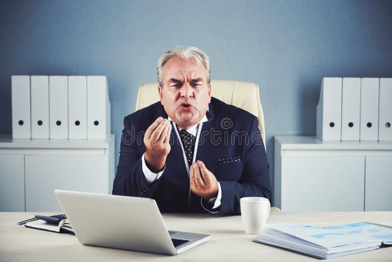 Hombre de negocios maduro enojado feroz que explica usando las manos imágenes de archivo libres de regalías