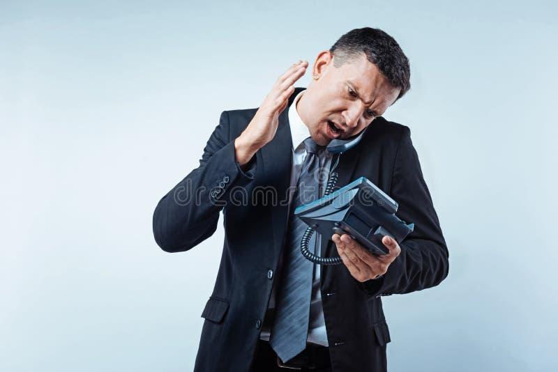 Hombre de negocios maduro enojado que grita en el socio en el teléfono foto de archivo libre de regalías